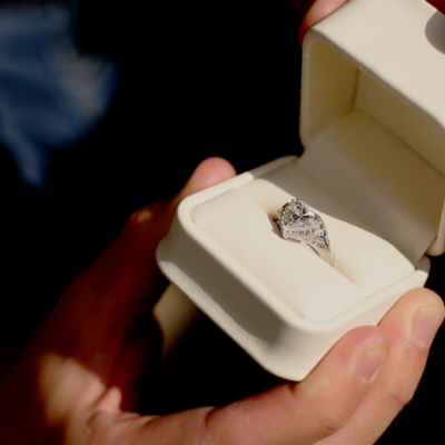 close up of mans hands holding a ring box with a heart shaped wedding ring in it