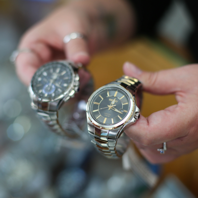 close up of hands holding two wrist watches
